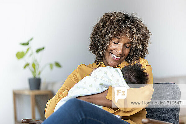 Glückliche Mutter sieht ihr Baby an,  während sie zu Hause auf einem Sessel sitzt