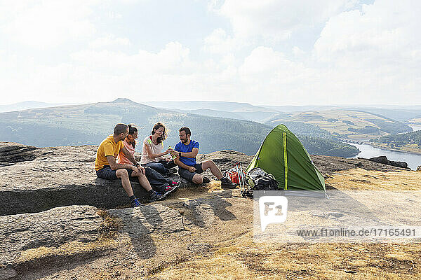 Male and female hiker friends camping on mountain top during vacations