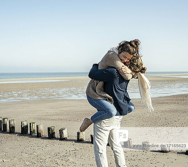 Young man picking up girlfriend and embracing at beach on sunny day