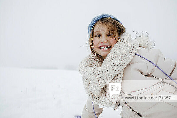 Playful girl smiling in warm clothing during winter