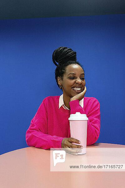 Lächelnde junge Geschäftsfrau mit Hand am Kinn  die einen wiederverwendbaren Kaffeebecher vor einer blauen Wand im Büro hält Lächelnde junge Geschäftsfrau mit Hand am Kinn, die einen wiederverwendbaren Kaffeebecher vor einer blauen Wand im Büro hält