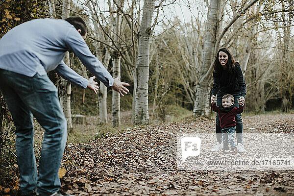 Eltern lehren Kleinkind Sohn Spaziergang im Wald im Herbst