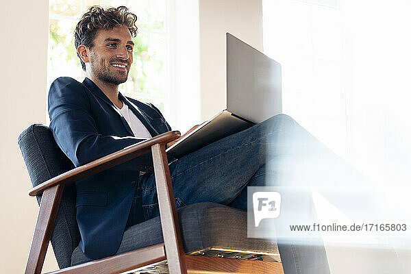 Smiling businessman using laptop while sitting on armchair at home