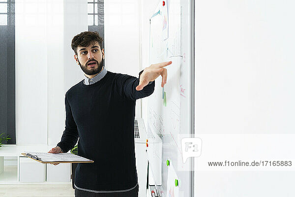 Businessman having presentation in office  pointing at whiteboard