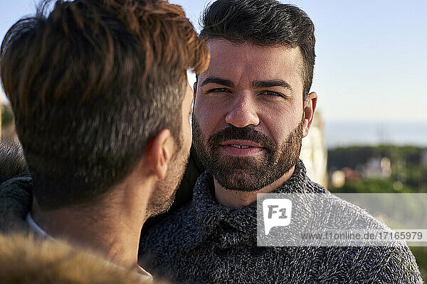 Close-up portrait of handsome man with boyfriend against clear sky