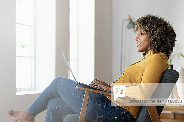 Thoughtful woman looking away while sitting with laptop on armchair at home
