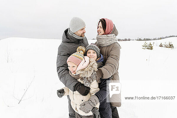 Family enjoying vacation on snow covered landscape against sky