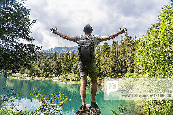 Carefree man carrying backpack standing with arms outstretched against Cauma Lake at Graubunden Canton  Switzerland