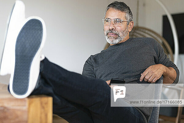 Thoughtful businessman using mobile phone while sitting with legs on table at home