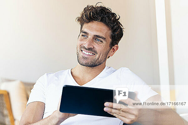 Thoughtful man with digital tablet looking away while sitting at home