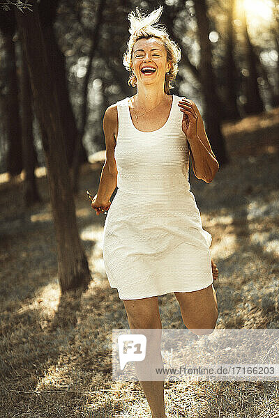 Cheerful woman running against trees in forest during sunset