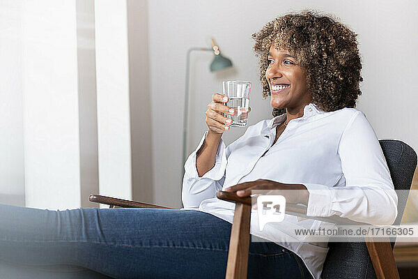 Smiling woman holding drinking water glass while sitting on armchair at home