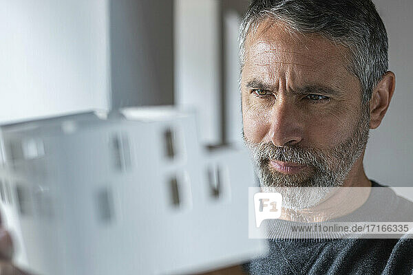 Architect examining architectural model while working at home