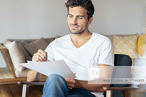 Man concentrating on paper while sitting on armchair at home