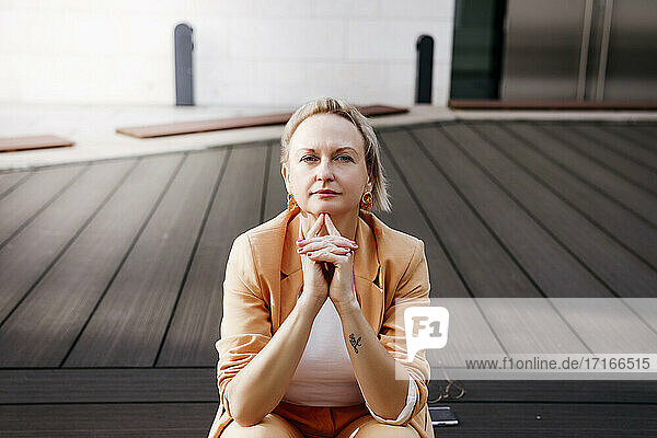 Mature female entrepreneur with hands clasped sitting on floorboard