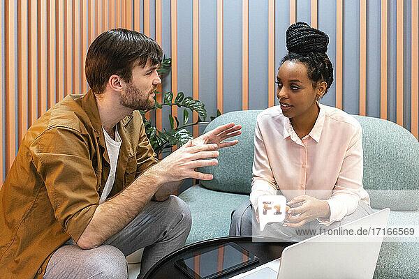 Kreative Geschäftsleute mit Laptop  die im Büro sitzen und diskutieren Kreative Geschäftsleute mit Laptop, die im Büro sitzen und diskutieren