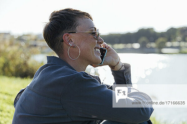 Young woman smiling while talking on mobile phone sitting at park