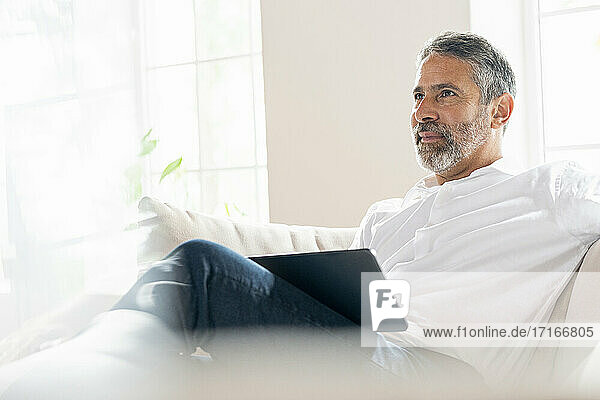 Thoughtful businessman sitting with digital tablet on sofa at home