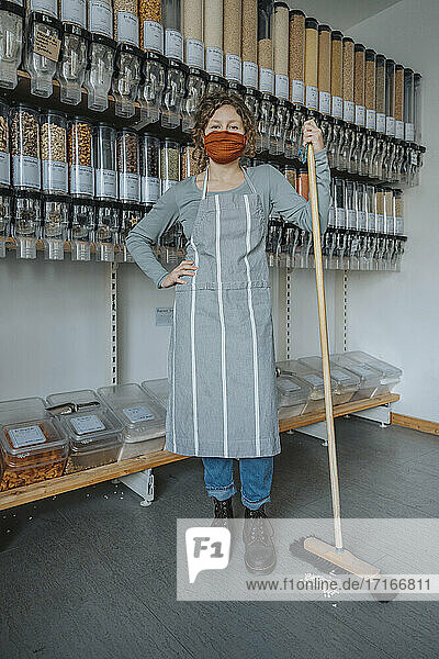 Female store clerk with hand on hip holding broom while standing in zero waste shop during COVID-19