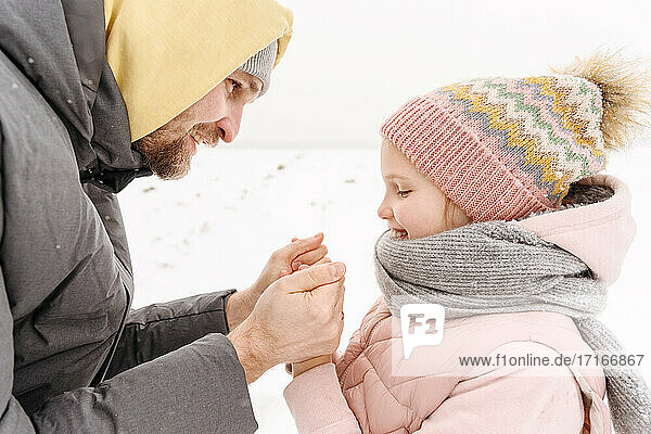 Close-up of father holding daughter's cold hands during winter