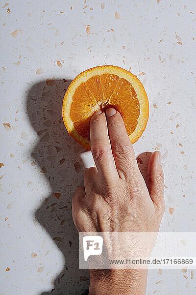 Woman's fingers in halved orange on modern terrazzo marble
