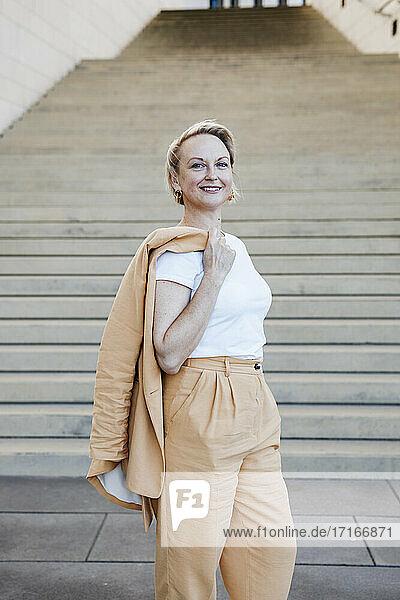 Smiling female entrepreneur holding blazer jacket while standing against staircase