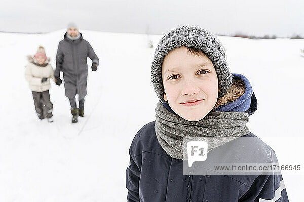 Boy standing on snow covered landscape with family in background