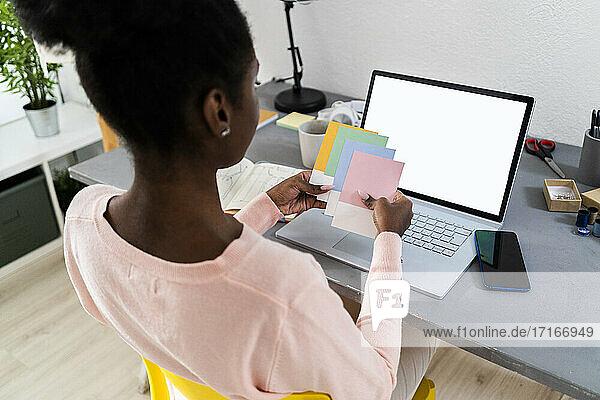 Modedesigner  der zu Hause im Büro sitzt und bunte Stoffmuster auswählt