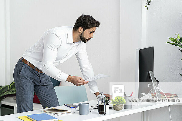 Male professional with paper document using computer while working in office