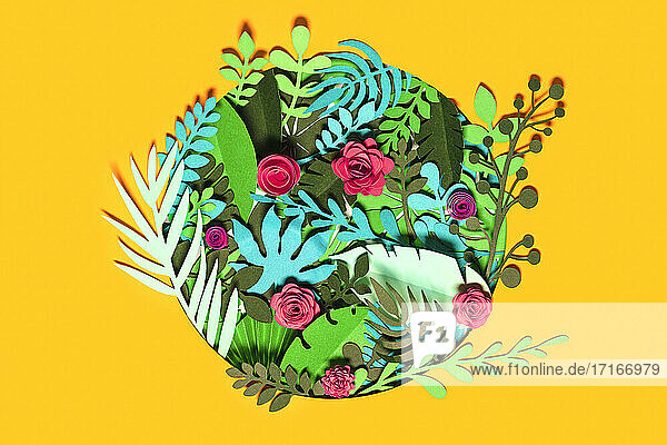 Green paper plants with flowers over yellow background