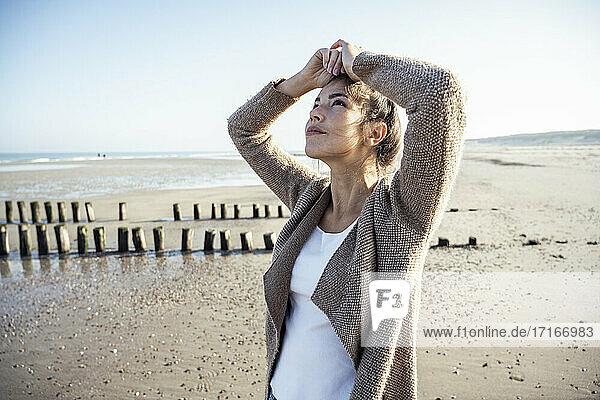 Nachdenkliche Frau  die am Strand gegen den Himmel blickt Nachdenkliche Frau, die am Strand gegen den Himmel blickt