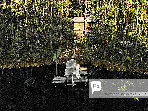 Drone shot of woman reading book while sitting on pier over lake in forest