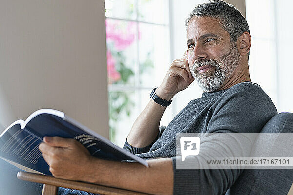 Businessman holding book while sitting on armchair at home