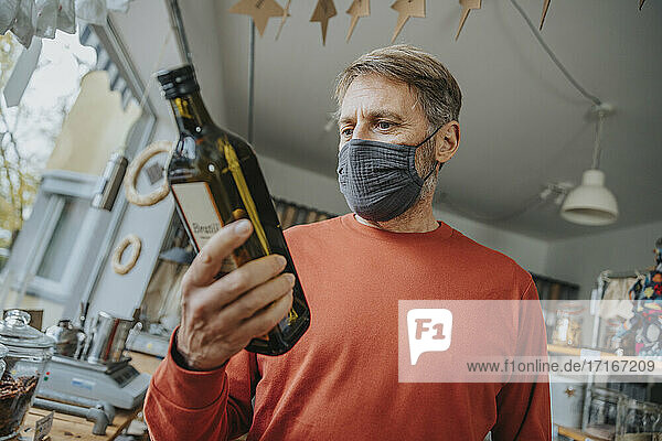 Mature male customer in mask looking at bottle while shopping in retail store during COVID-19