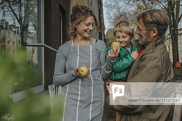 Smiling saleswoman selling apple to father and son at retail store