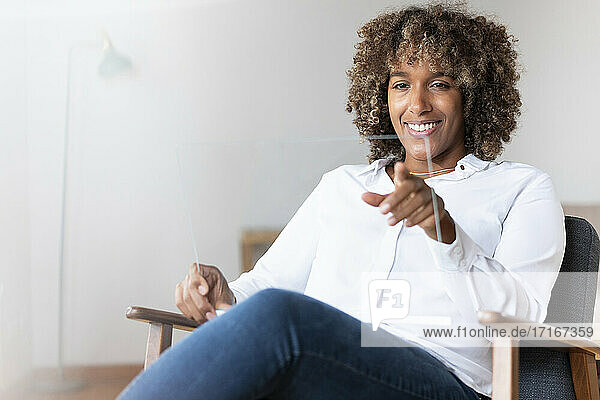 Smiling woman using transparent screen device while sitting on armchair at home
