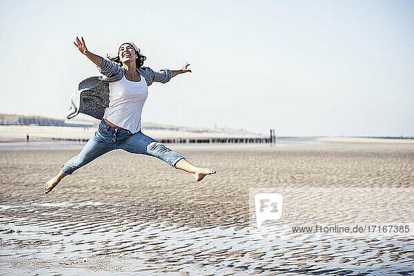 Fröhliche junge Frau  die an einem sonnigen Tag über nassen Sand springt Fröhliche junge Frau, die an einem sonnigen Tag über nassen Sand springt