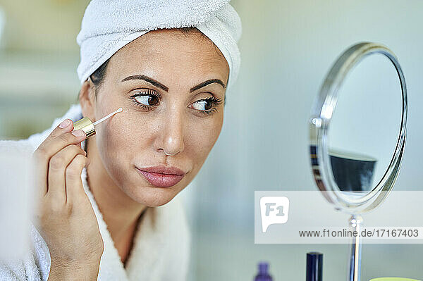 Beautiful woman applying beauty serum while looking in mirror at home