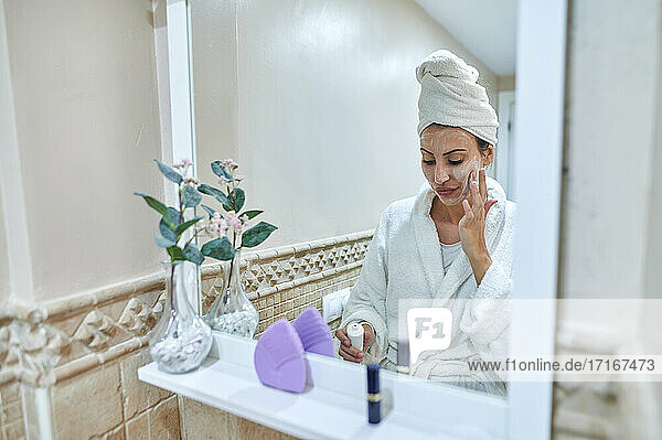 Reflection of woman applying face cream in bathroom