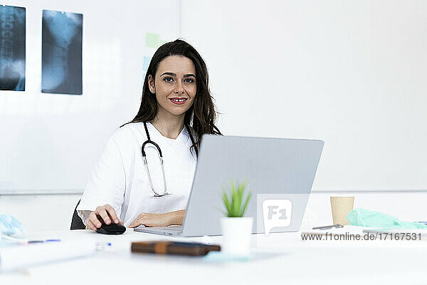 Smiling female doctor using laptop in clinic