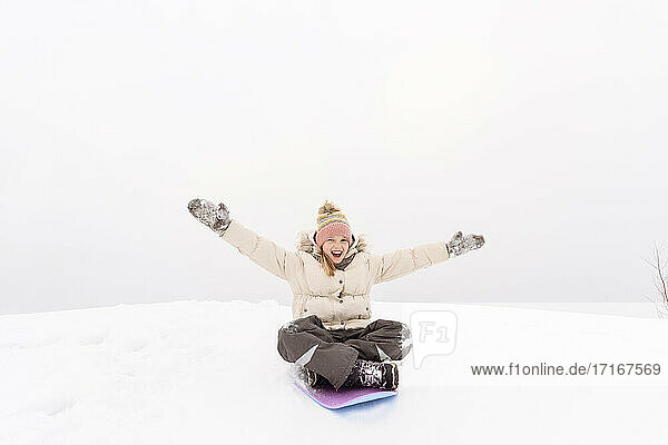 Carefree girl with arms outstretched sledding on snowy hill against sky