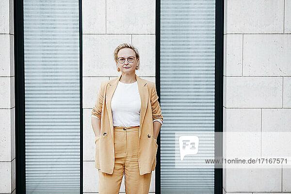 Selbstbewusste Geschäftsfrau mit Händen in den Taschen  die an der Wand steht