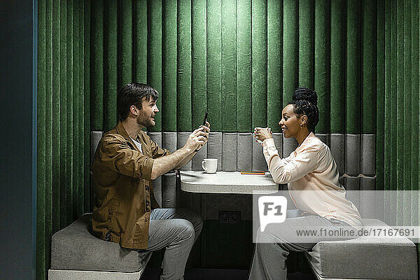 Geschäftsmann  der eine Kollegin fotografiert  während er in der Cafeteria seines Arbeitsplatzes sitzt Geschäftsmann, der eine Kollegin fotografiert, während er in der Cafeteria seines Arbeitsplatzes sitzt