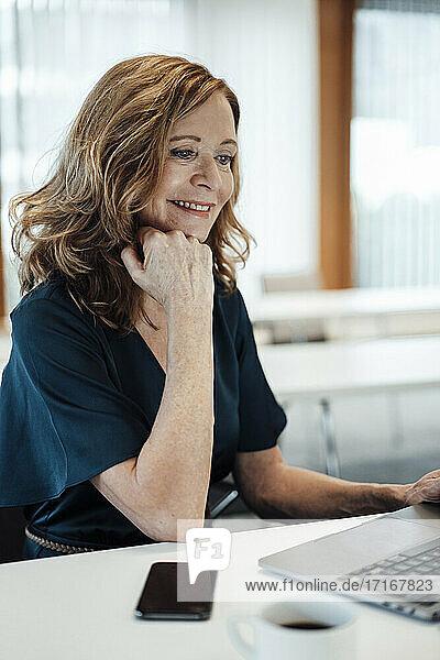 Unternehmerin mit Hand am Kinn bei der Arbeit am Laptop im Büro