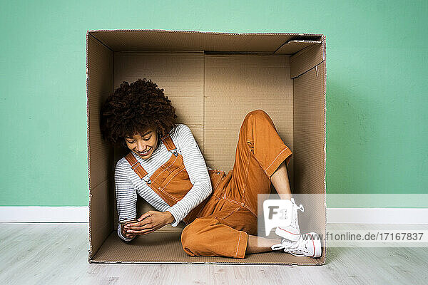 Smiling woman using mobile phone while sitting in cardboard box at new home