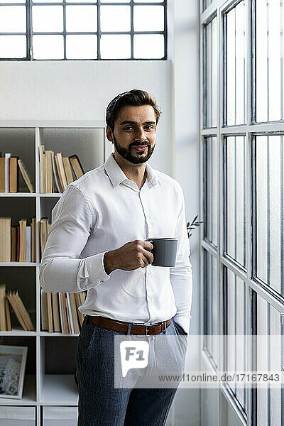 Smiling male entrepreneur with hands in pockets holding coffee cup in office