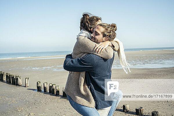 Freund umarmt Freundin beim Abholen am Strand während des Wochenendes Freund umarmt Freundin beim Abholen am Strand während des Wochenendes