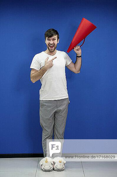 Fröhlicher Geschäftsmann in Einhorn-Pantoffeln  der auf ein Megaphon an einer blauen Wand im Büro zeigt Fröhlicher Geschäftsmann in Einhorn-Pantoffeln, der auf ein Megaphon an einer blauen Wand im Büro zeigt