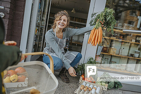 Female clerk showing carrots to female customer at organic shop