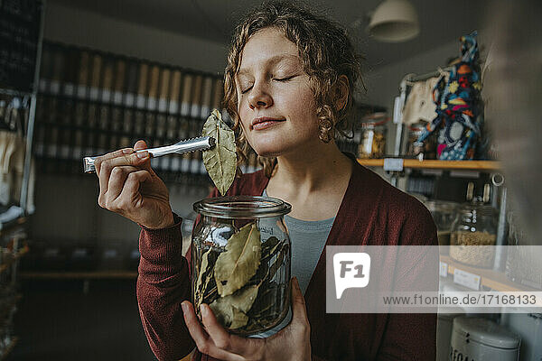 Female clerk with eyes closed smelling bay leaf while working in zero waste shop